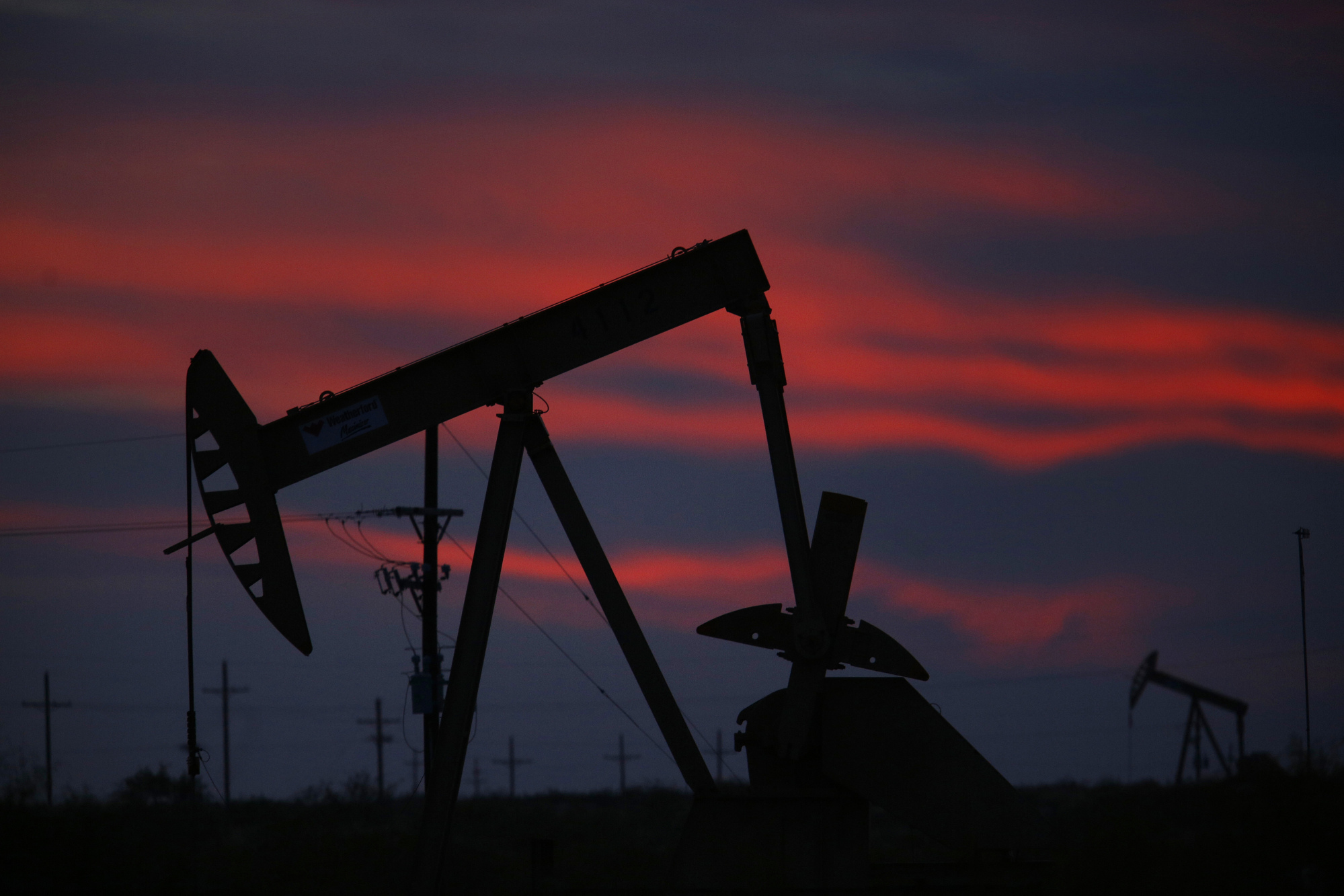 The silhouette of an electric oil pump jack is seen at dusk in the oil fields surrounding Midland, Texas, U.S., on Tuesday, Nov. 7, 2017. Photographer: Luke Sharrett/Bloomberg