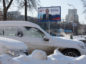An election campaign billboard poster featuring incumbent Russian President Vladimir Putin stands beyond snow covered automobiles in Moscow, Russia. Photographer: Andrey Rudakov/Bloomberg