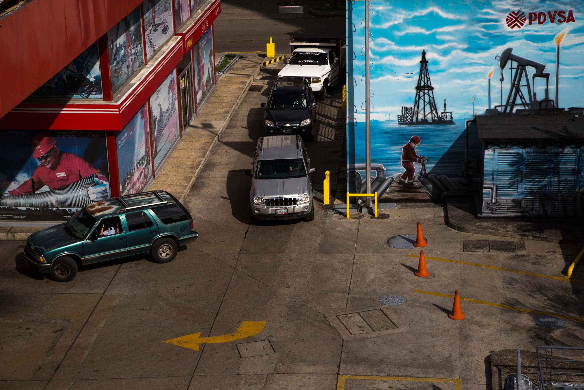 Vehicles wait in line for fuel at a Petroleos de Venezuela SA (PDVSA) gas station in Caracas. Photographer: Wil Riera/Bloomberg