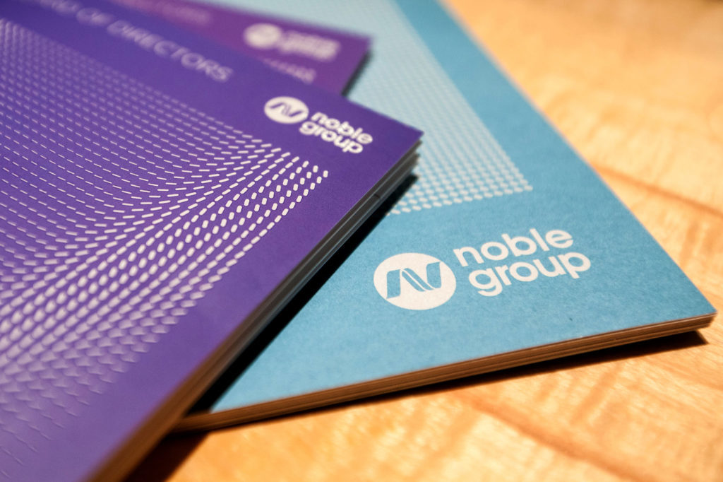 Noble Group Ltd. booklets sit on a table before a news conference during an investor day in Singapore, on Monday, Aug. 17, 2015. Noble GroupLtd. pledged to increase operating profit to more than $2 billion in the next three to five years as Asia's largest commodity trader sought to reassure investors about its long-term prospects. Photographer: Nicky Loh/Bloomberg