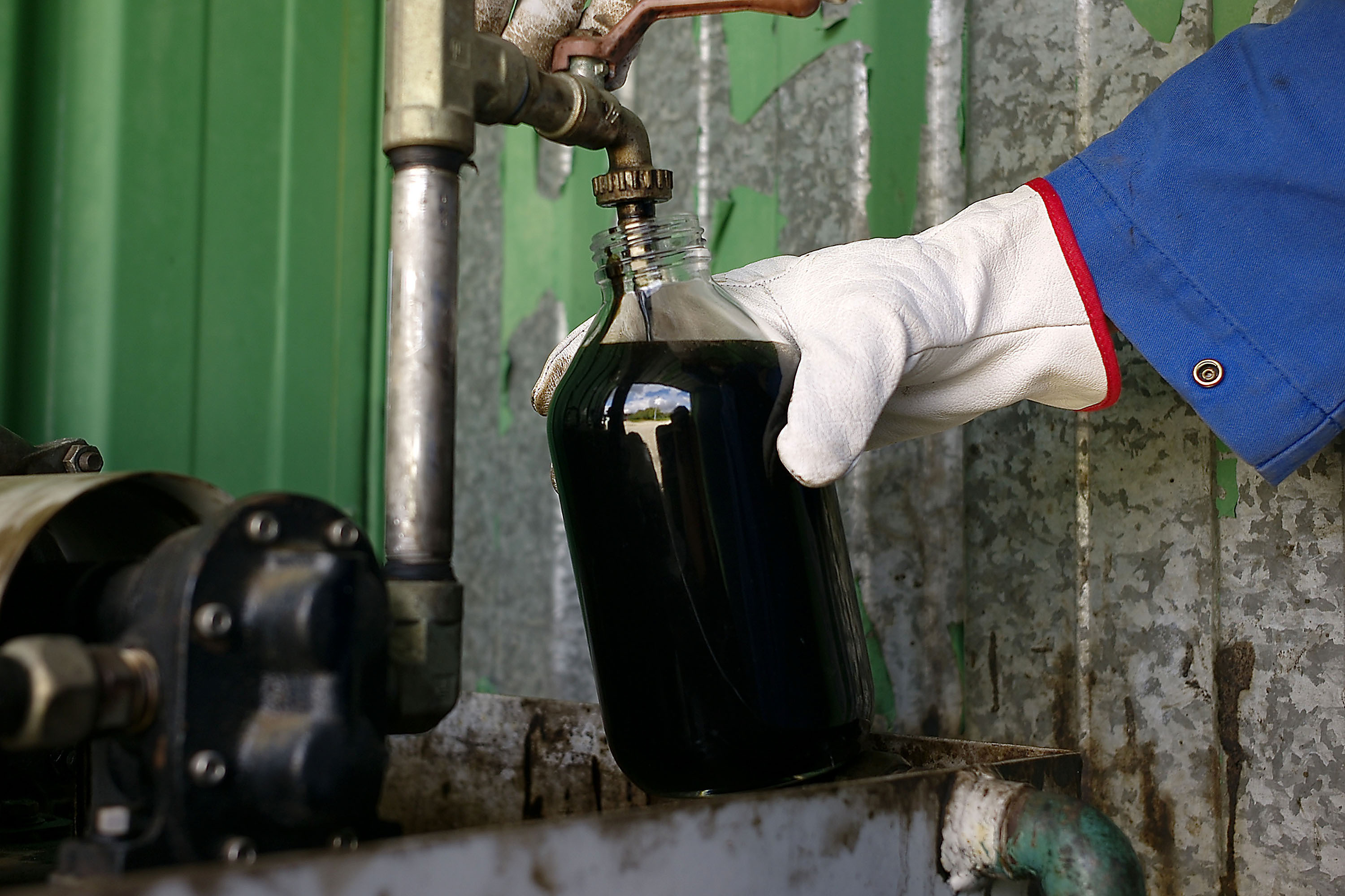 An employee takes a sample of crude oil to be sent for analysis. Photographer: Antoine Antoniol/Bloomberg