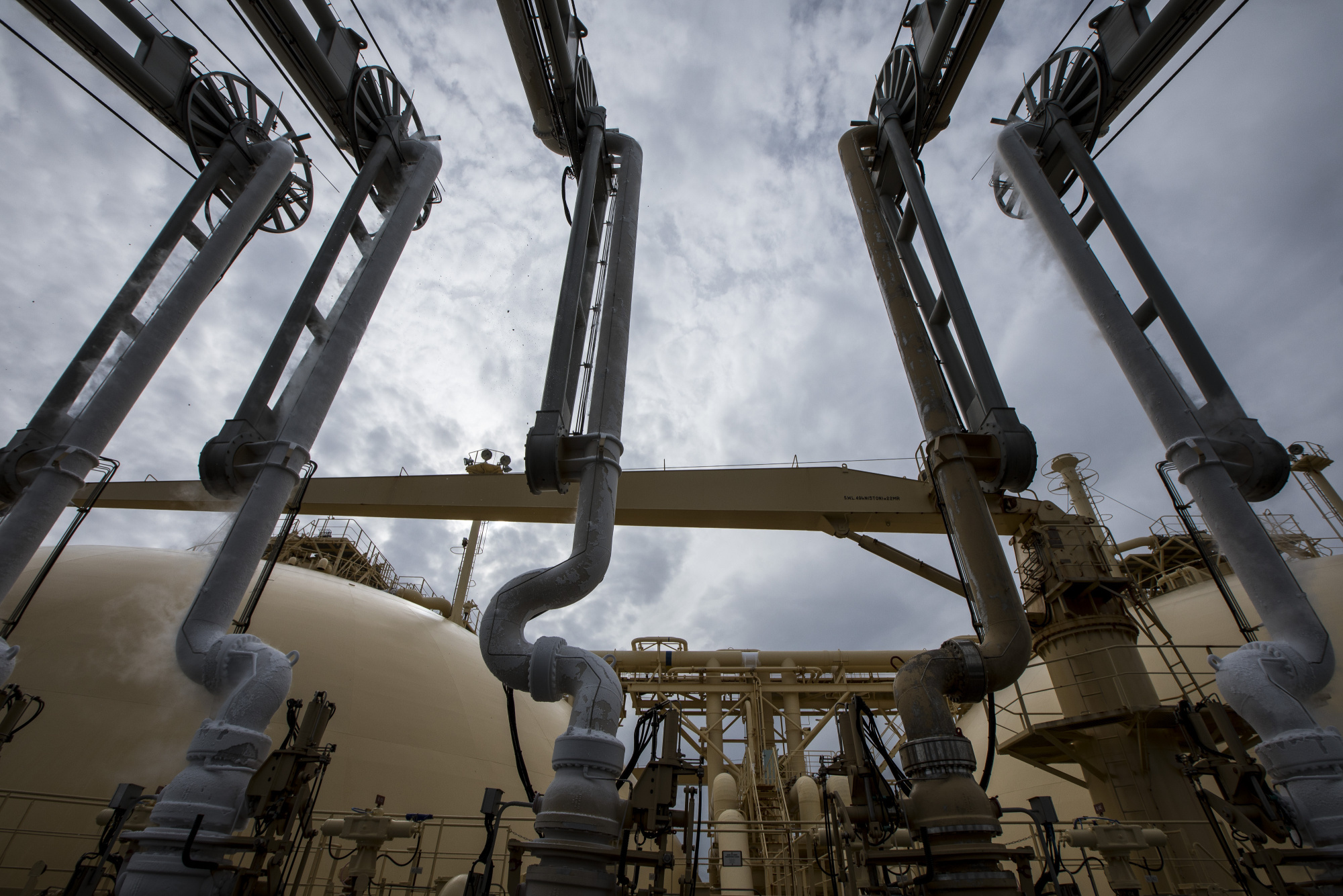 Liquefied natural gas (LNG) dispenses through pipes on-board the Gallina LNG tanker after docking at the National Grid Plc's Grain LNG plant on the Isle of Grain in Rochester, U.K. Photographer: Jason Alden/Bloomberg
