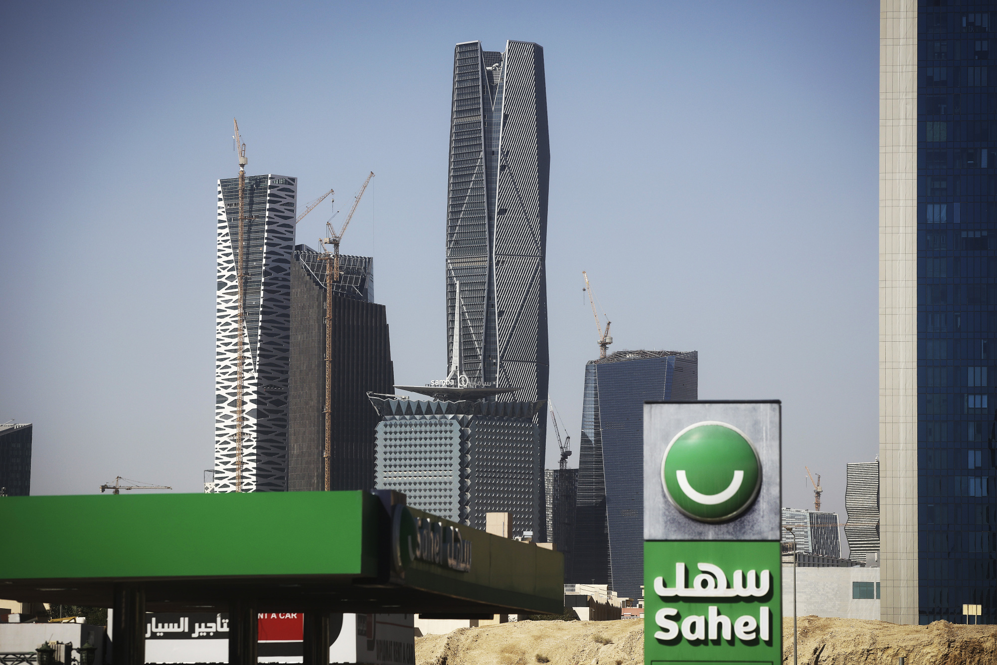 A Sahel petrol station, operated by Tas'helat Marketing Co Ltd., stands in front of buildings under construction including offices, apartments, hotels, conference centres, mosque and entertainment venues, at the King Abdullah Financial District (KAFD)in Riyadh, Saudi Arabia, on Thursday, Dec. 1, 2016. The King Abdullah Financial District, known as the KAFD and about 70 percent complete, has been beset by construction delays since work began in the Saudi capital in 2006. Photographer: Simon Dawson/Bloomberg