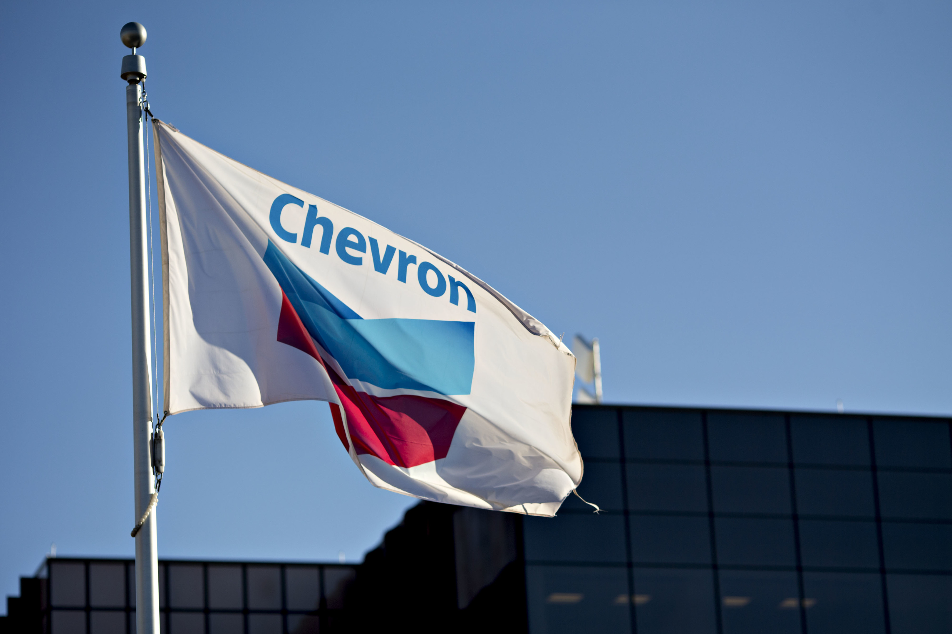 A Chevron Corp. flag flies outside an office building in Midland, Texas, U.S., on Thursday, March 1, 2018. Photographer: Daniel Acker/Bloomberg