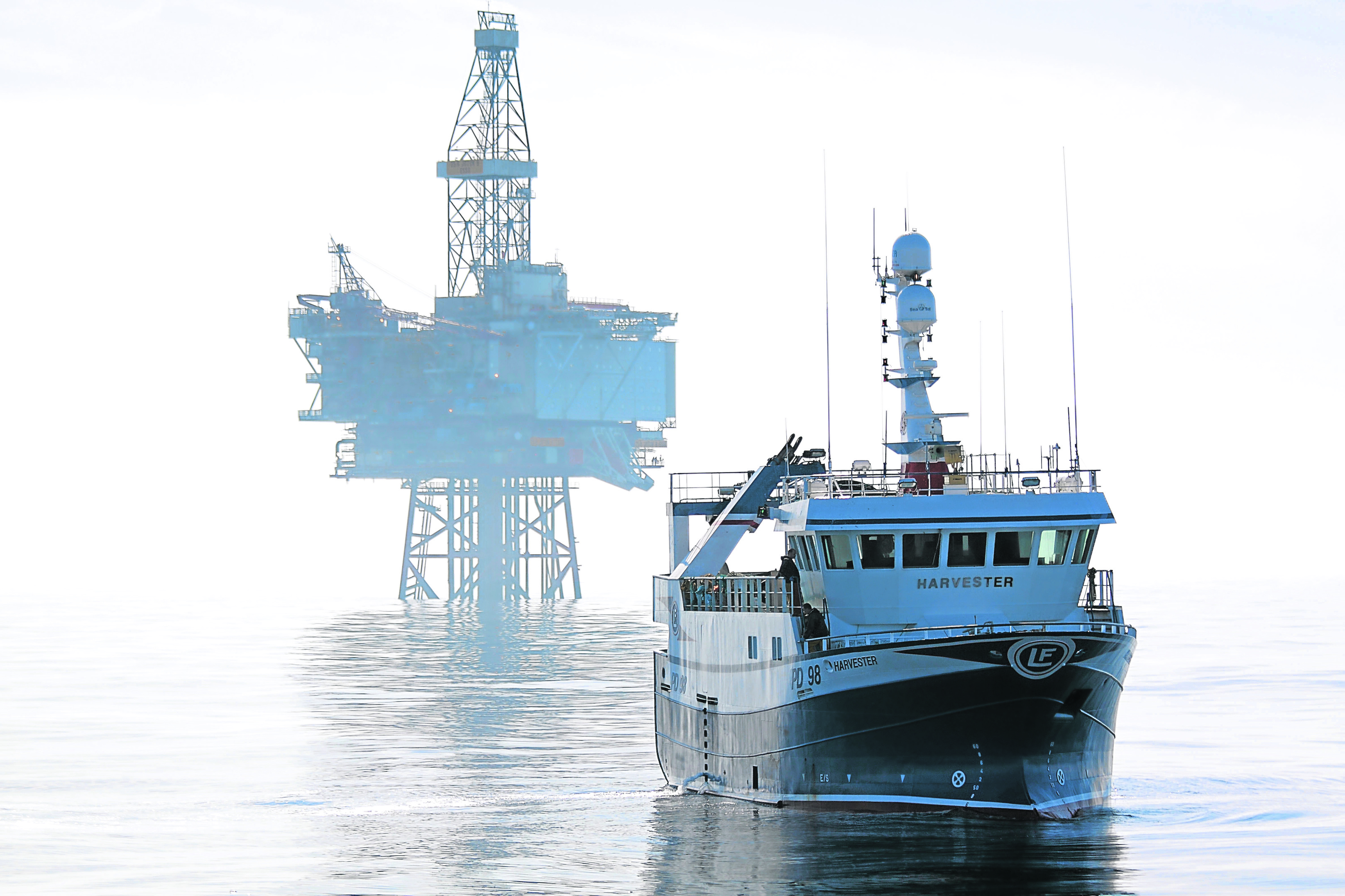 E45R11 Fishing vessel Harvester and the Jotun B oil production platform. North Sea May 2010