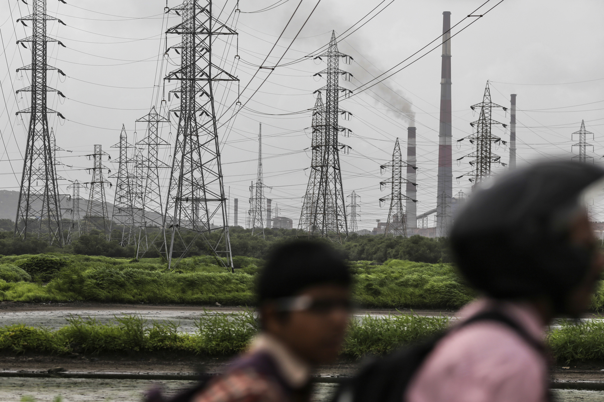 Smoke rises from a chimney as electricity pylons stand at the Tata Power Co. Trombay Thermal Power Station in Mumbai, India, on Saturday, Aug. 5, 2017. Nearly six months after his turbulent elevation to run India's biggest conglomerate, Tata Chairman Natarajan Chandrasekaran is assembling a team of dealmakers to refocus some of the group's biggest businesses, expand its financial services and consumer businesses and sell or merge dozens of smaller units, according to interviews with senior executives. Photographer: Dhiraj Singh/Bloomberg