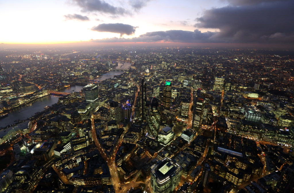 Lights illuminate the windows of skyscrapers and commercial office buildings as they stand near the banks of the River Thames in this aerial photograph taken over the City of London, in London, U.K. Photographer: Chris Ratcliffe/Bloomberg