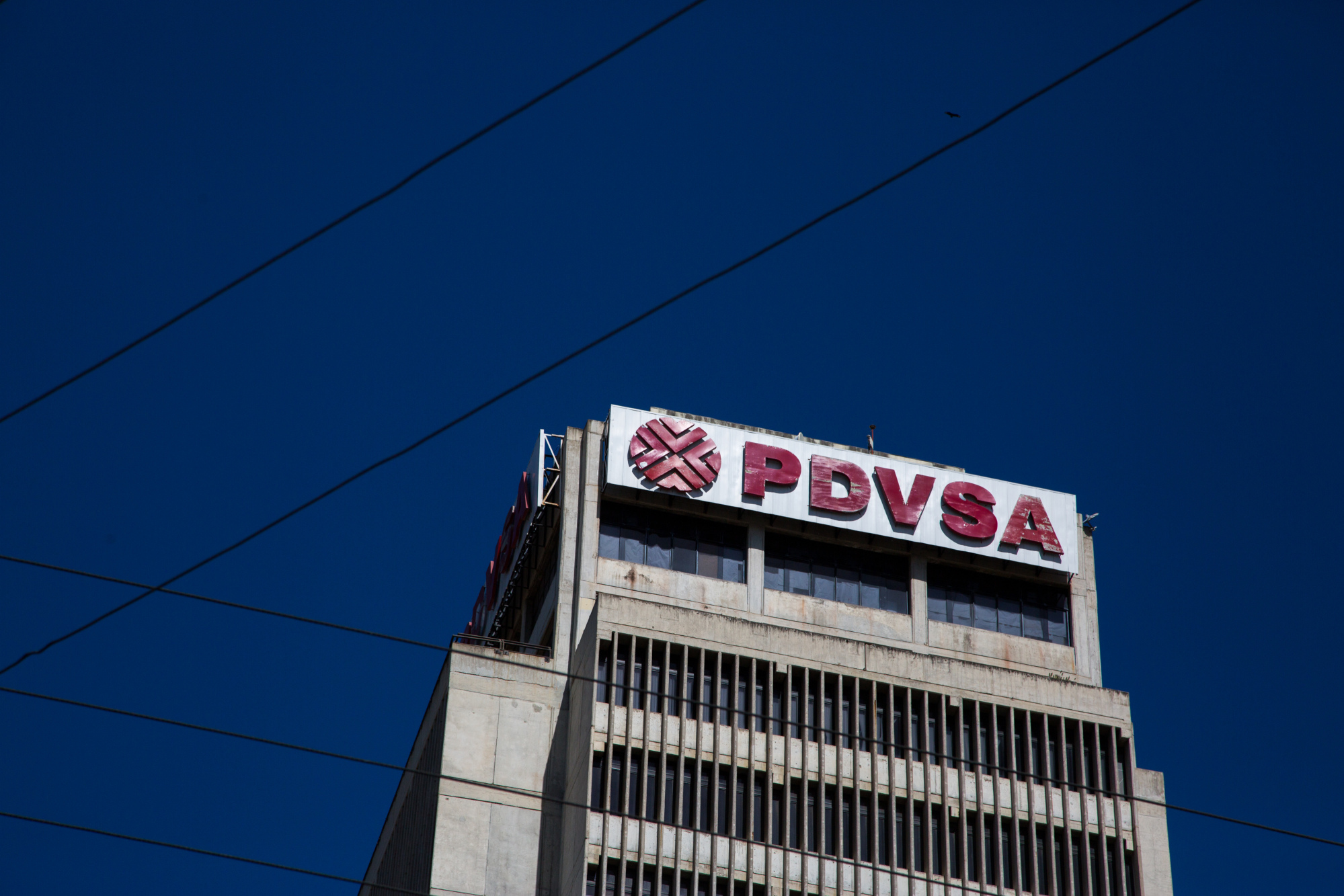 Petroleos de Venezuela SA (PDVSA) signage is displayed on a building in Puerto La Cruz, Anzoategui State, Venezuela, on Wednesday, Feb. 7, 2018. Hunger is hastening the ruin of Venezuelan's oil industry as workers grow too weak and hungry for heavy labor. Absenteeism and mass resignations mean few are left to produce the oil that keeps the tattered economy functioning. Photographer: Wil Riera/Bloomberg
