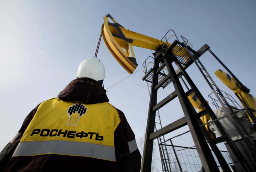 Workers inspect an oil pumping jack, also known as a 'nodding donkey' at a pumping site, operated by Rosneft PJSC, in the Samotlor oilfield near Nizhnevartovsk, Russia, on Wednesday, March 22, 2017. Russia's largest oil field, so far past its prime that it now pumps almost 20 times more water than crude, could be on the verge of gushing profits again for Rosneft PJSC. Photographer: Andrey Rudakov/Bloomberg