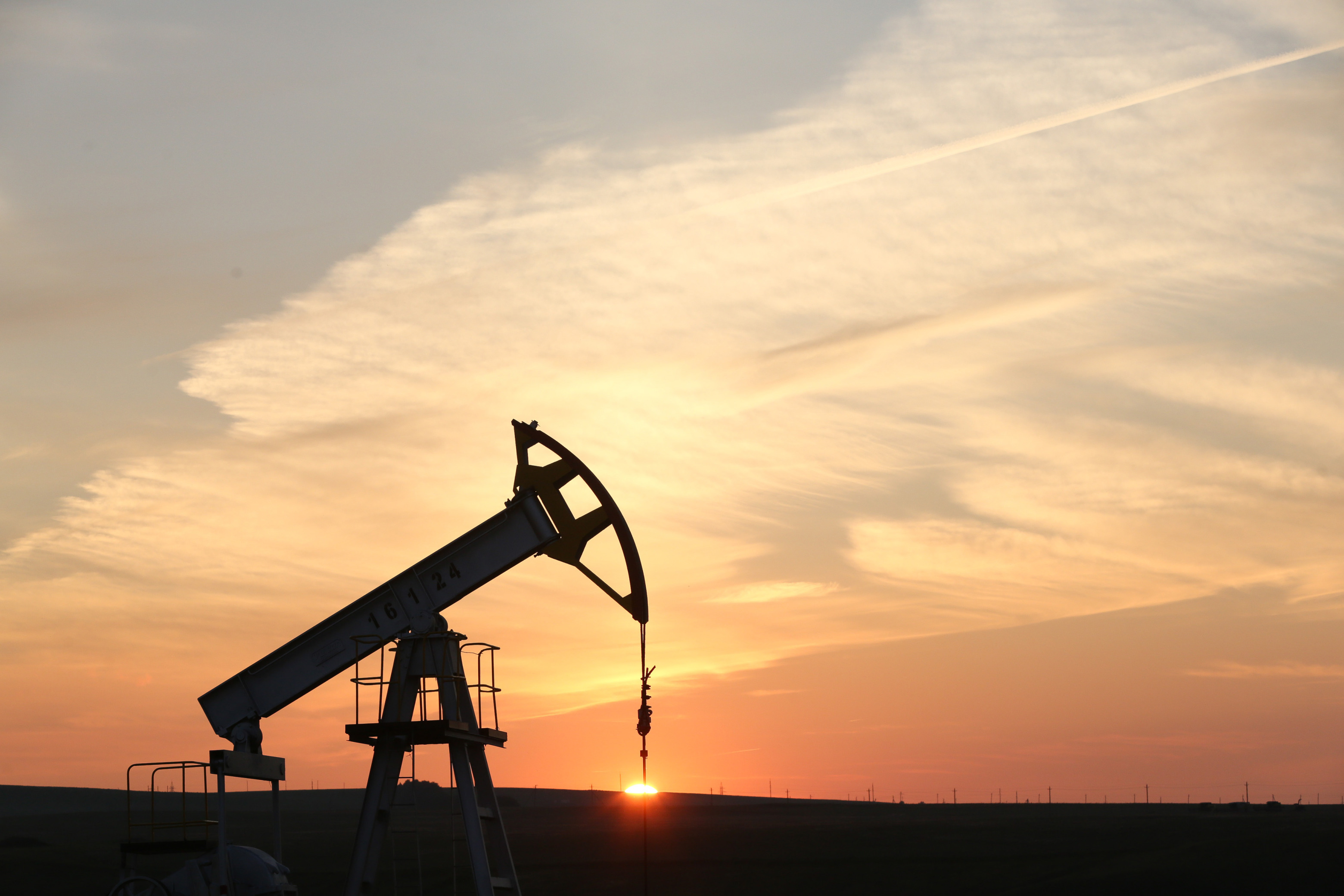 "An oil pumping unit, also known as a ""nodding donkey"" or pumping jack, operates at sunset at a drilling site"