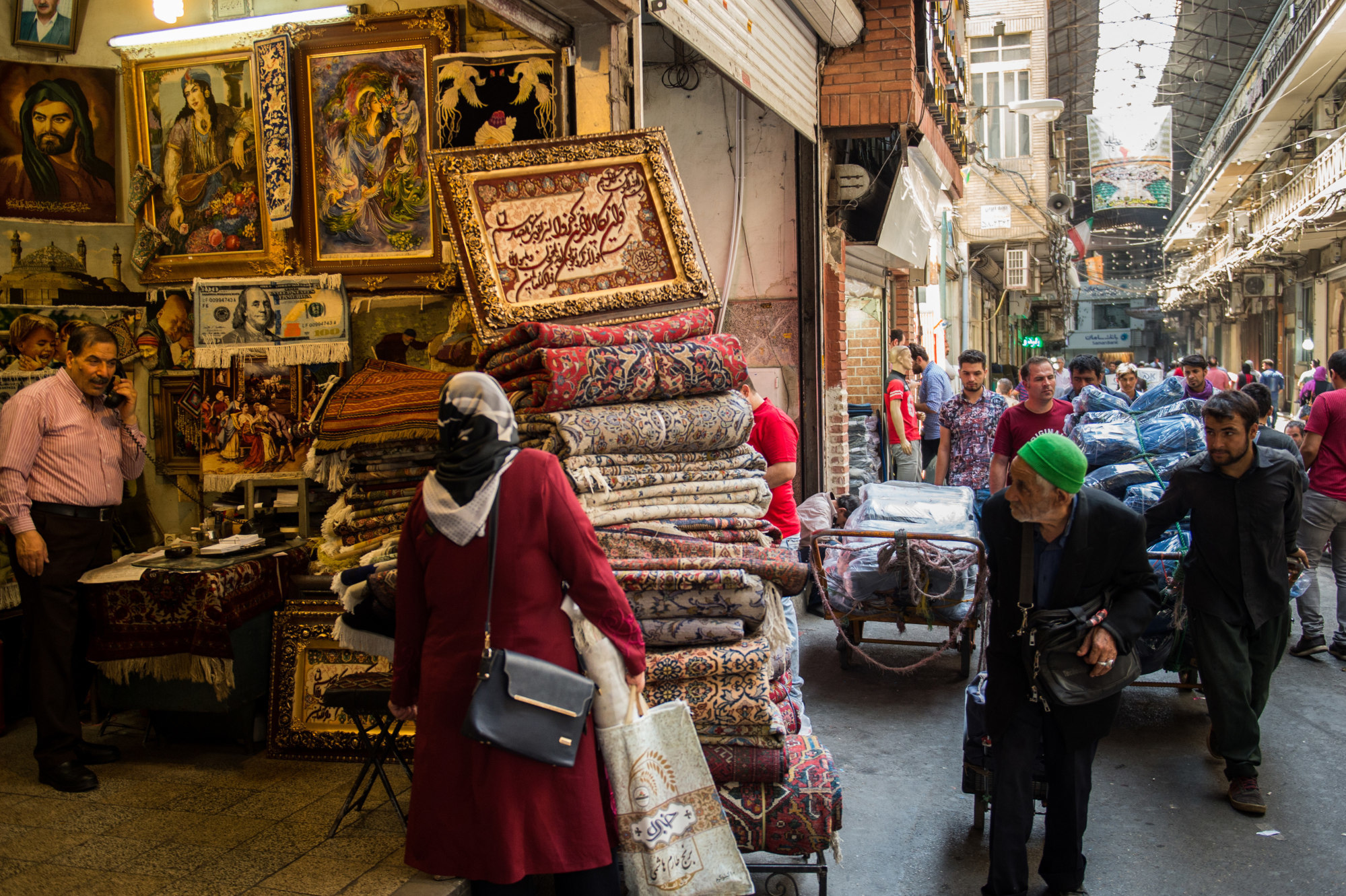 Carpet traders wheel their wares past a store selling Persian rugs inside the Grand Bazaar in Tehran, on Aug. 6. Photographer: Ali Mohammadi/Bloomberg