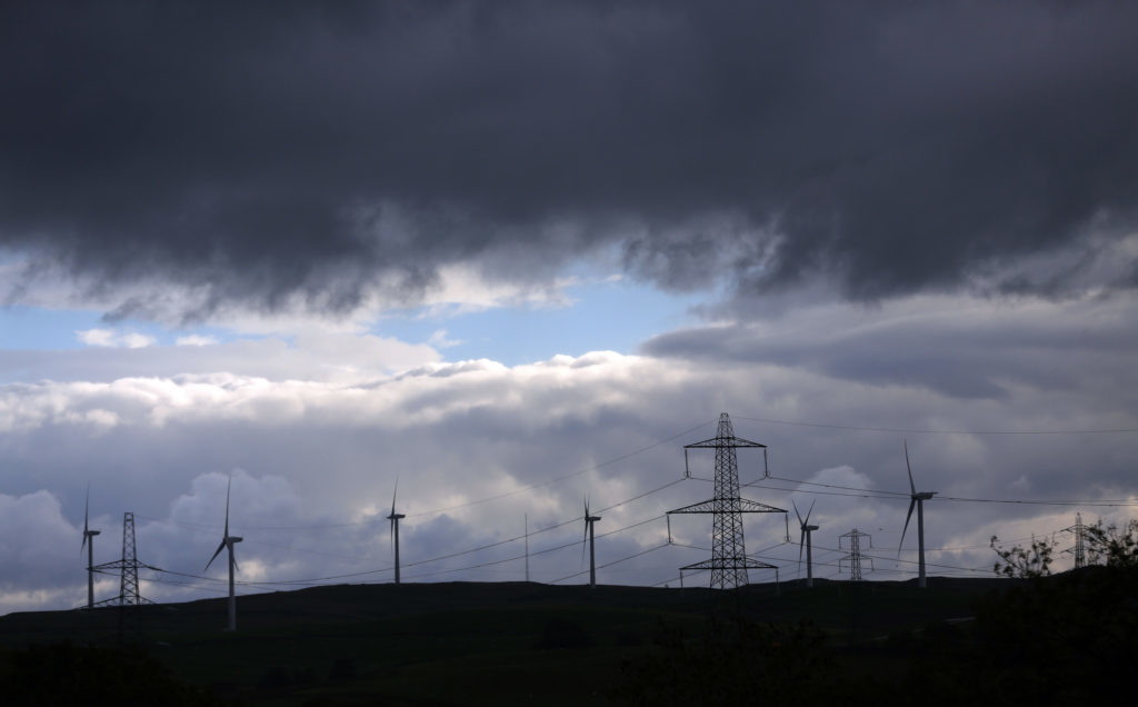 Wind turbines stand on the horizon near a National Grid Plc electricity pylons in Kendal, U.K. Photographer: Paul Thomas/Bloomberg