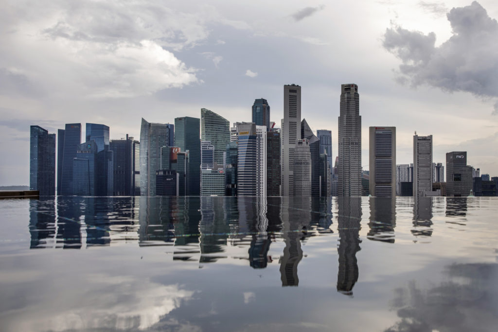 Commercial buildings standing in the central business district are reflected in a rooftop pool in Singapore, on Wednesday, June 13, 2018.  Photographer: Brent Lewin/Bloomberg