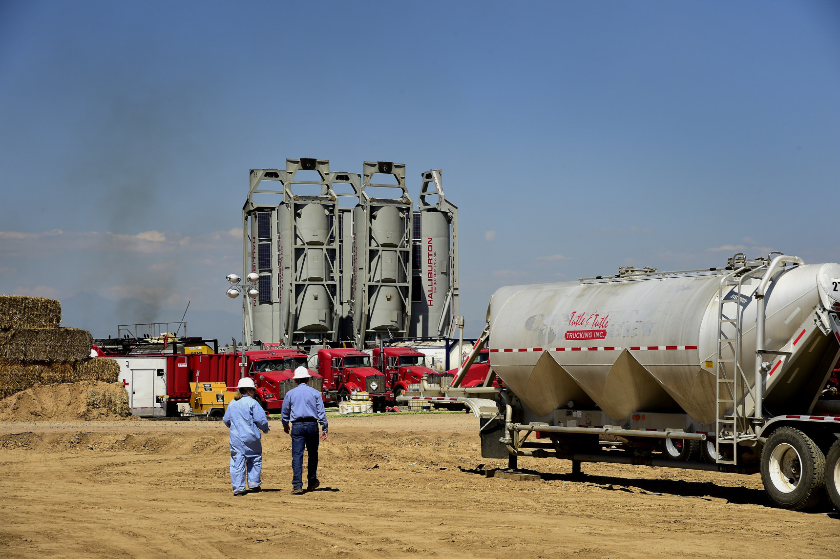 "Workers walk towards Halliburton Co. ""sand castles"" at an Anadarko Petroleum Corp. hydraulic fracturing (fracking) site north of Dacono, Colorado, U.S. Photographer: Jamie Schwaberow/Bloomberg"