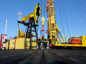 Workers perform a well-workover operation at a multiple well platform, operated by Rosneft PJSC, in the Samotlor oilfield near Nizhnevartovsk, Russia, on Monday, March 20, 2017. Russia's largest oil field, so far past its prime that it now pumps almost 20 times more water than crude, could be on the verge of gushing profits again for Rosneft PJSC. Photographer: Andrey Rudakov/Bloomberg