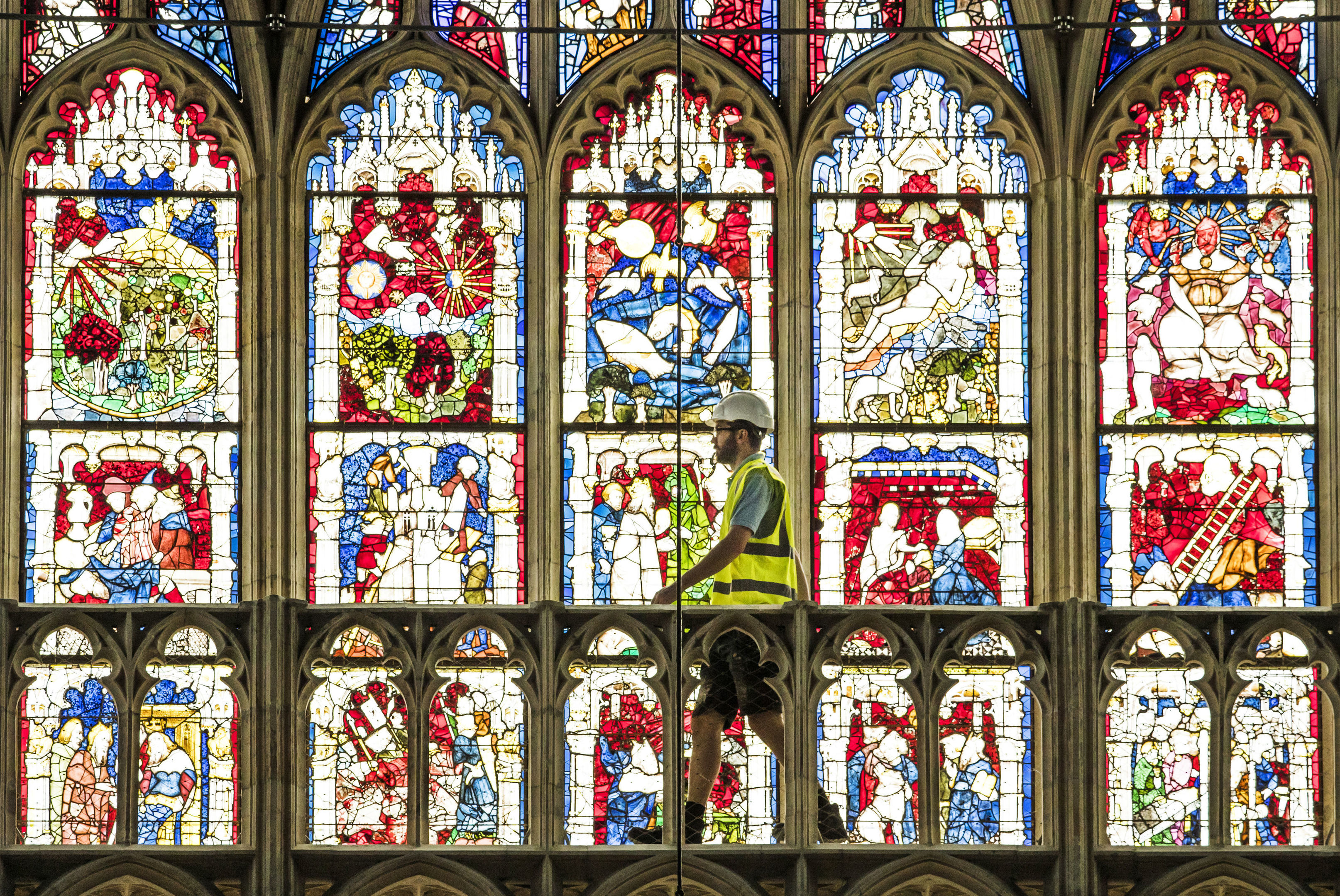 Lead Labourer Andy Bracegirdle walks past the 600-year old Great East Window in York Minster, as work is completed in a decade-long project to conserve and restore the largest expanse of medieval stained glass in the country. PRESS ASSOCIATION Photo. Picture date: Thursday May 17, 2018. The work has been part of an £11.5m programme which has included extensive work by the Minster's stonemasons to repair and replace hundreds of stones at the cathedral's East End, which houses the window. See PA story HERITAGE Minister. Photo credit should read: Danny Lawson/PA Wire