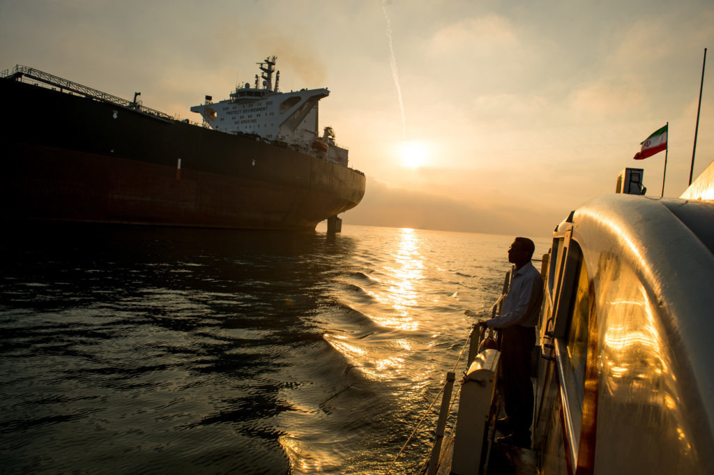 A support vessel flying an Iranian national flag sails alongside the oil tanker 'Devon' as it prepares to transport crude oil to export markets in Bandar Abbas, Iran. Photographer: Ali Mohammadi/Bloomberg