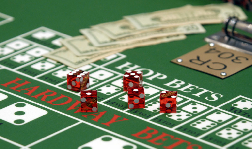 Cash and dice sit on a craps table at the Sands Casino Resort in Bethlehem, Pennsylvania, U.S. Photographer: Bradley C. Bower/Bloomberg