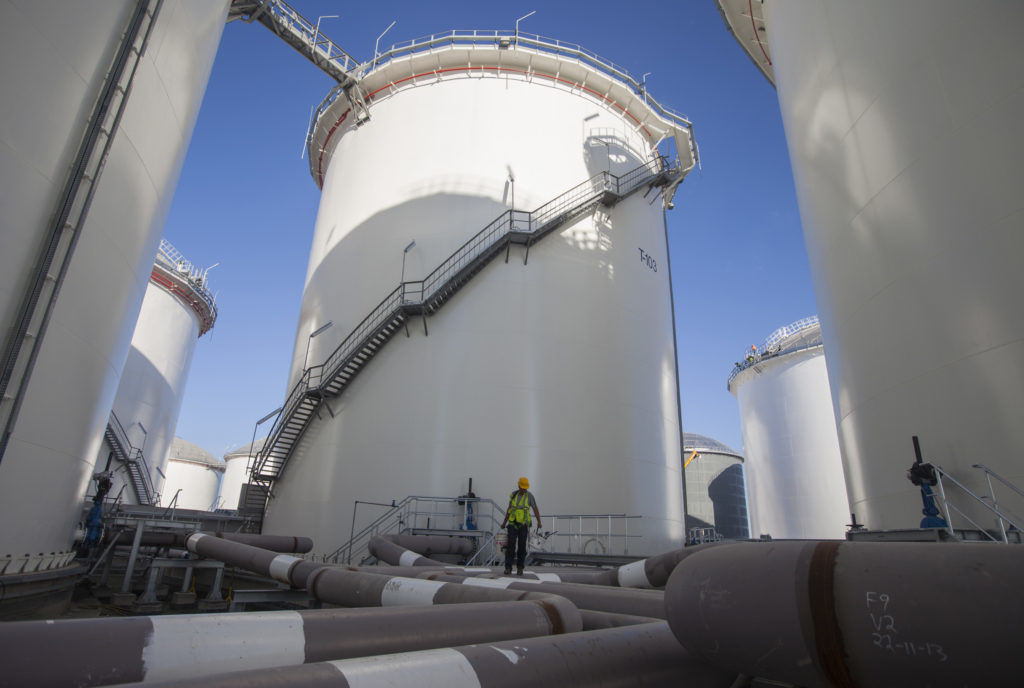 A construction worker stands on pipes at the base of fuel storage tanks. Photographer: Andrew Caballero-Reynolds