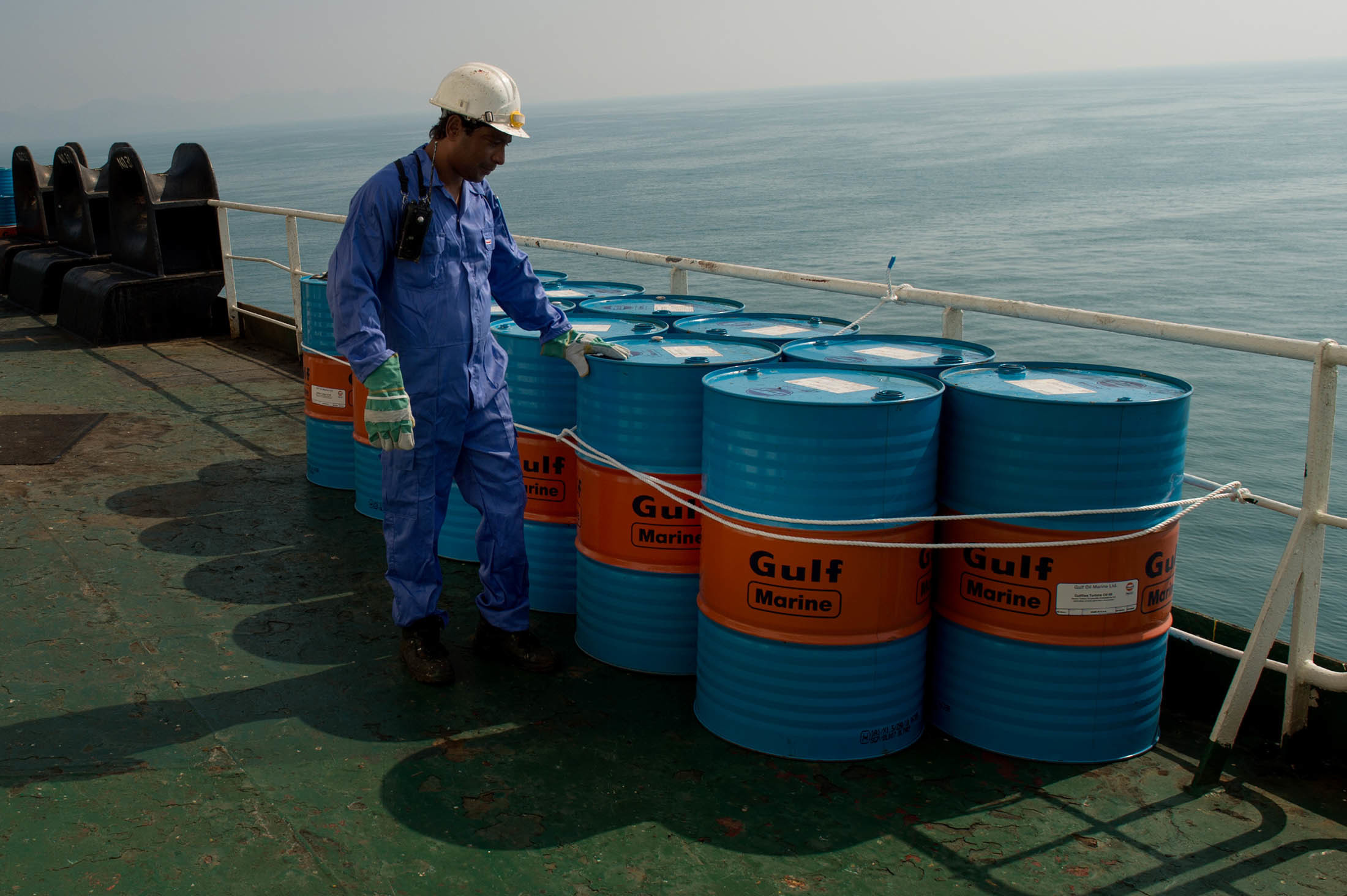 A crew man secures Gulf Marine oil drums on the deck of oil tanker 'Devon' as it prepares to transport crude oil from Kharq Island to India in Bandar Abbas, Iran, on Friday, March 23, 2018. Geopolitical risk is creeping back into the crude oil market. Photographer: Ali Mohammadi/Bloomberg