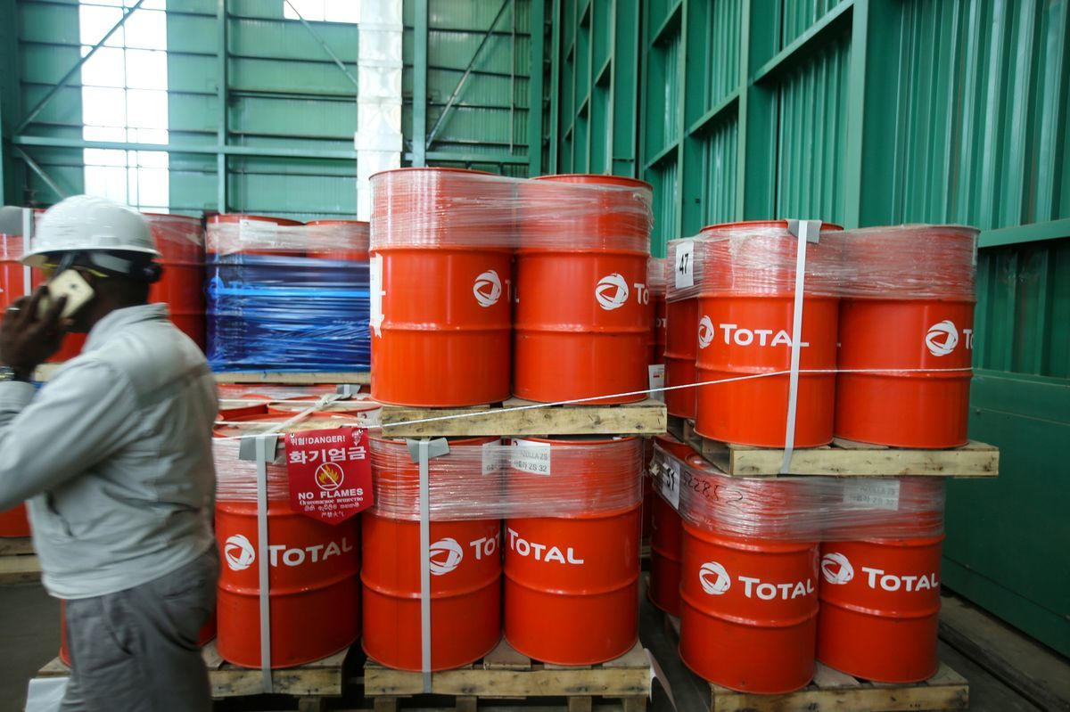 A worker speaks on a mobile telephone as he passes Total SA branded oil drums stored in the warehouse at the Ladol free trade zone port in Lagos, Nigeria, on Tuesday, May 22, 2018. Ladol, a logistics hub for the offshore oil industry in Lagos, Nigeria, is mulling a stock-market listing and corporate bonds to expand its facilities and get more business from major production companies. Photographer: George Osodi/Bloomberg