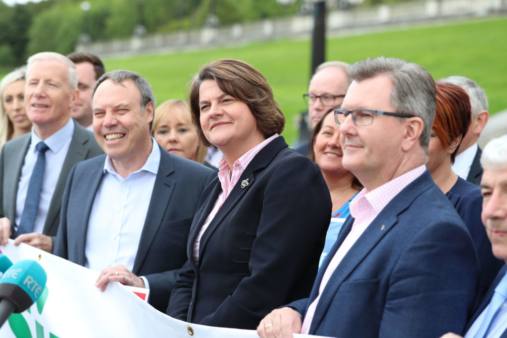 DUP leader Arlene Foster unveils a banner with party colleagues outside Parliament Buildings at Stormont in Belfast: Liam McBurney/PA Wire