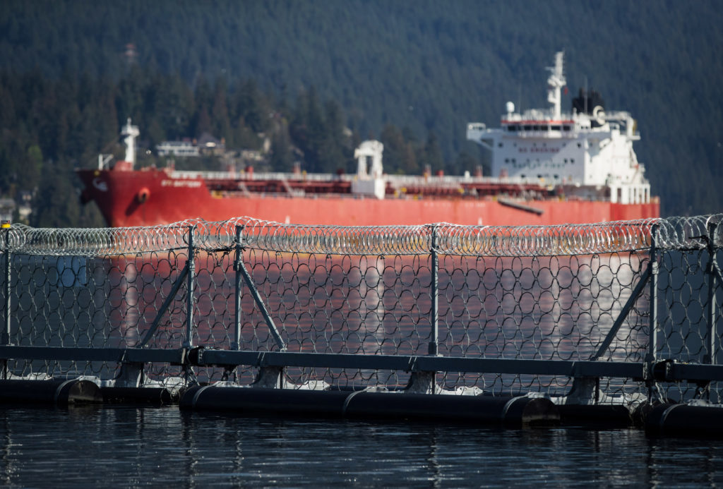"""A razor wire security fence floats in front of the STI Battery oil and chemical tanker during an emergency response exercise in Burrard Inlet at the Kinder Morgan Inc. Westridge Marine Terminal in Burnaby, British Columbia, Canada, on Wednesday, Sept. 19, 2018. A Canadian court's decision to nullify approval of the Trans Mountain Expansion Project will increase crude-by-rail transport in the near term and will likely have a """"negative impact on Canadian output growth in the longer term,"""" the International Energy Agency said earlier this month. Photographer: Darryl Dyck/Bloomberg"""
