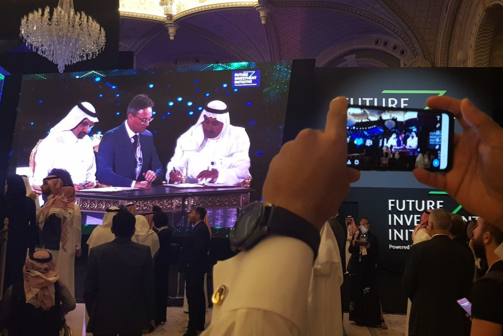 Jeremy Weir, chief executive officer of Trafigura Group, center, signs a deal at the Future Investment Initiative (FII) conference at the Ritz Carlton Hotel in Riyadh, Saudi Arabia, on Tuesday, Oct. 23, 2018. Photographer: Javier Blas/Bloomberg