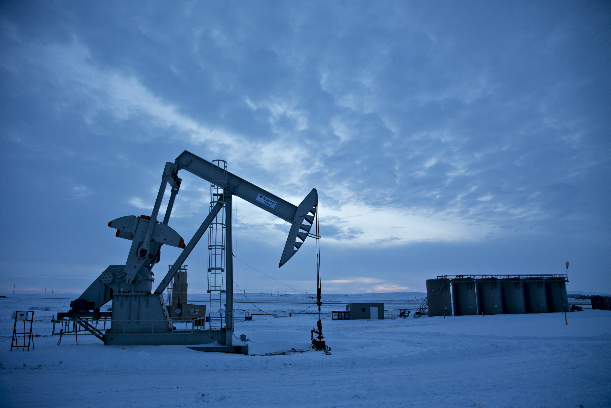 A pumpjack operates above an oil well in the Bakken Formation outside Williston, North Dakota, U.S., on Friday, March 9, 2018. When oil sold for $100 a barrel, many oil towns dotting the nation's shale basins grew faster than its infrastructure and services could handle. Since 2015, as oil prices floundered, Williston has added new roads, including a truck route around the city, two new fire stations, expanded the landfill, opened a new waste water treatment plant and started work on an airport relocation and expansion project. Photographer: Daniel Acker/Bloomberg