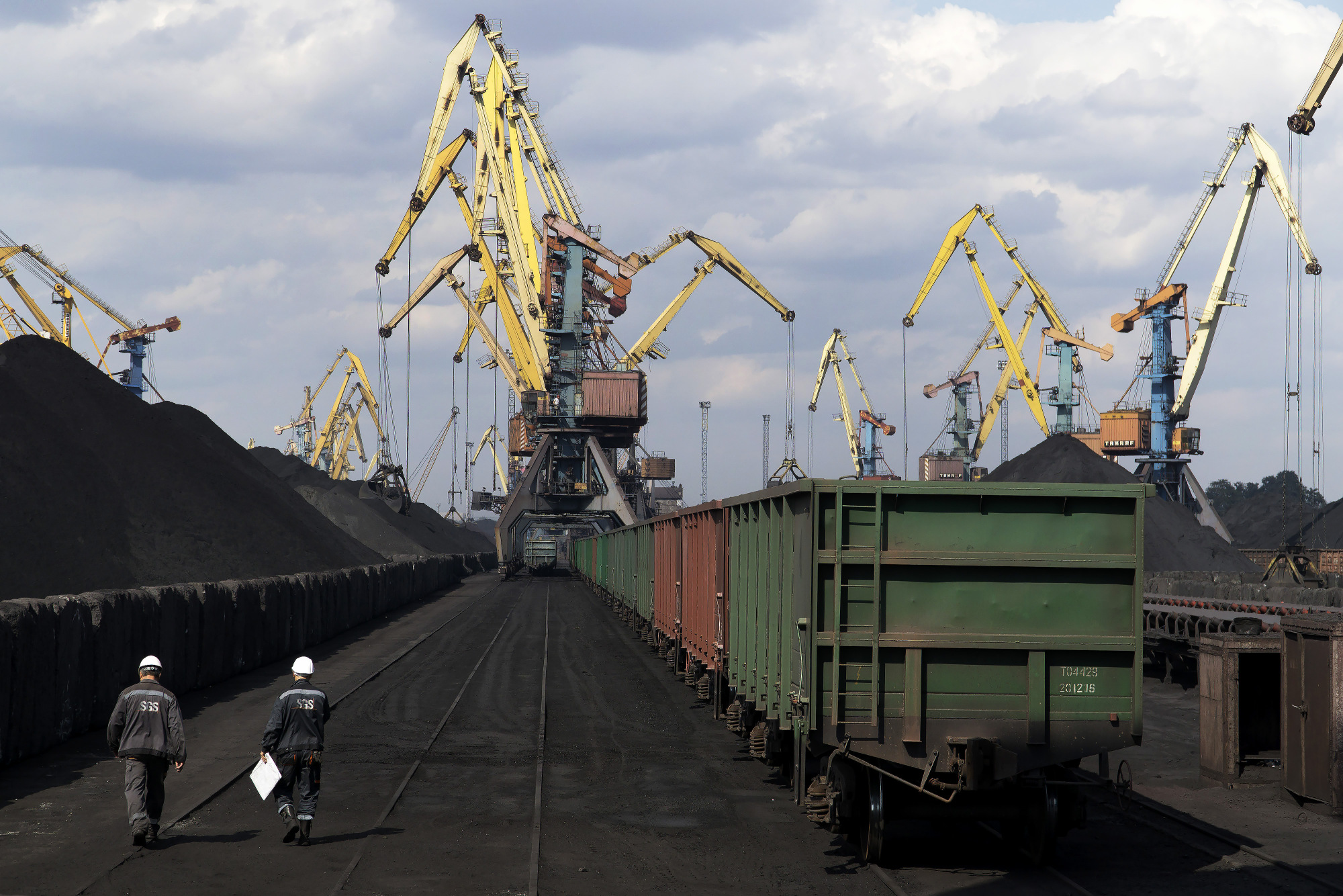 Workers pass freight wagons waiting to transport a shipment of coal from U.S. supplier at Yuzhny Port, near Odessa, Ukraine, in Sept. 2017. Photographer: Vincent Mundy/Bloomberg