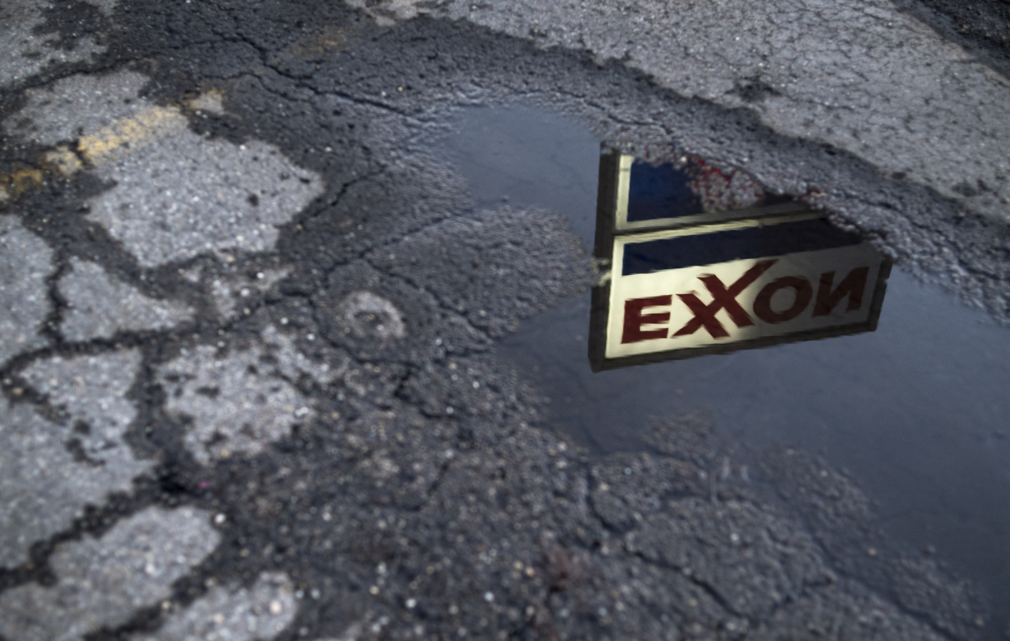 Exxon Mobil Corp. signage is reflected in a puddle at a gas station in Nashport, Ohio, U.S., on Friday, Jan. 26, 2018.  Photographer: Ty Wright/Bloomberg