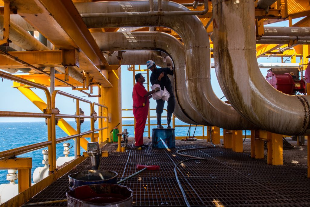 Workers clean oil leaks from pipes aboard an offshore oil platform in the Persian Gulf's Salman Oil Field, operated by the National Iranian Offshore Oil Co., near Lavan island, Iran, on Thursday, Jan. 5. 2017.  Photographer: Ali Mohammadi/Bloomberg