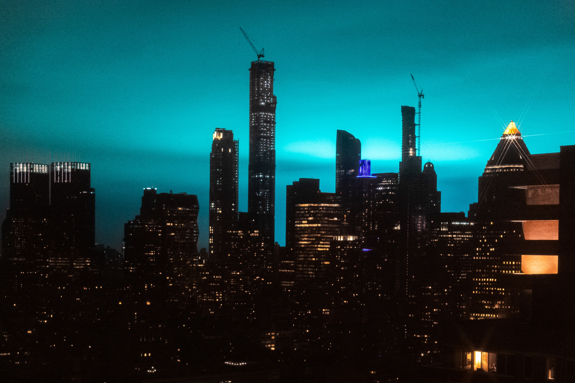Buildings stand as the night sky is illuminated by blue light in New York on Dec. 27, 2018. Photographer: Jeenah Moon/Bloomberg