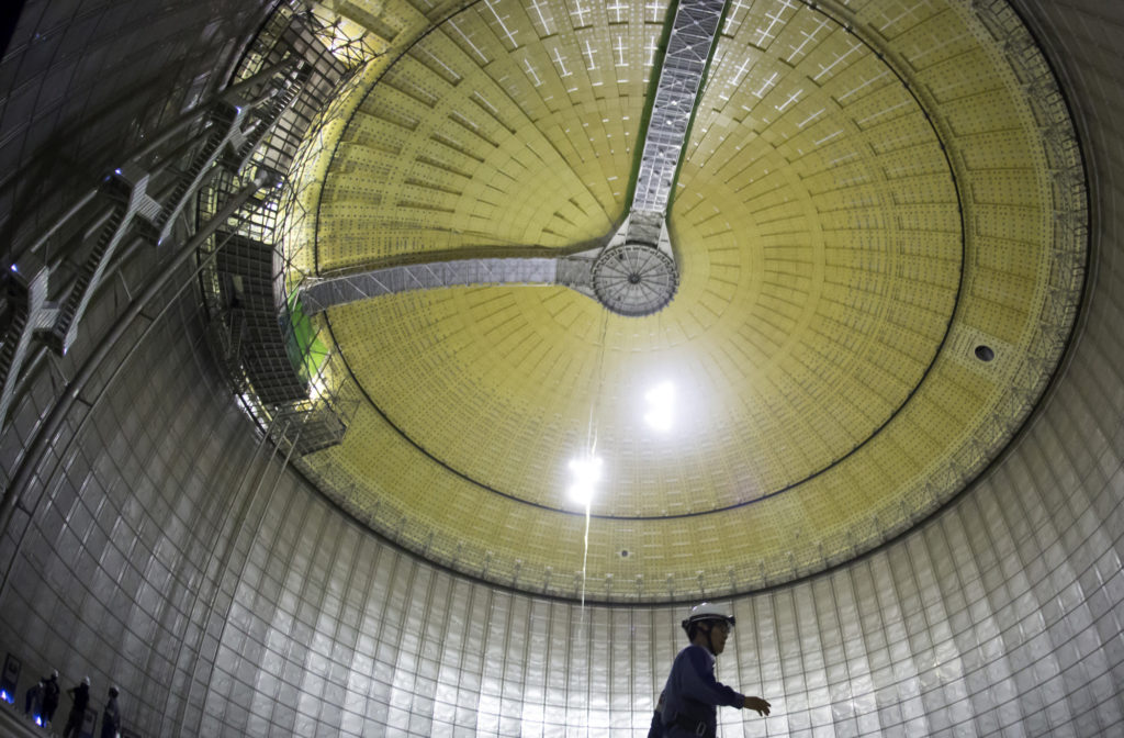 A Tokyo Electric Power Co. (Tepco) employee walks inside the company's liquefied natural gas (LNG) storage tank as it stands under construction at the Futtsu gas-fired thermal power plant in Futtsu, Chiba Prefecture, Japan, on Monday, Sept. 10, 2018.  Photographer: Tomohiro Ohsumi/Bloomberg
