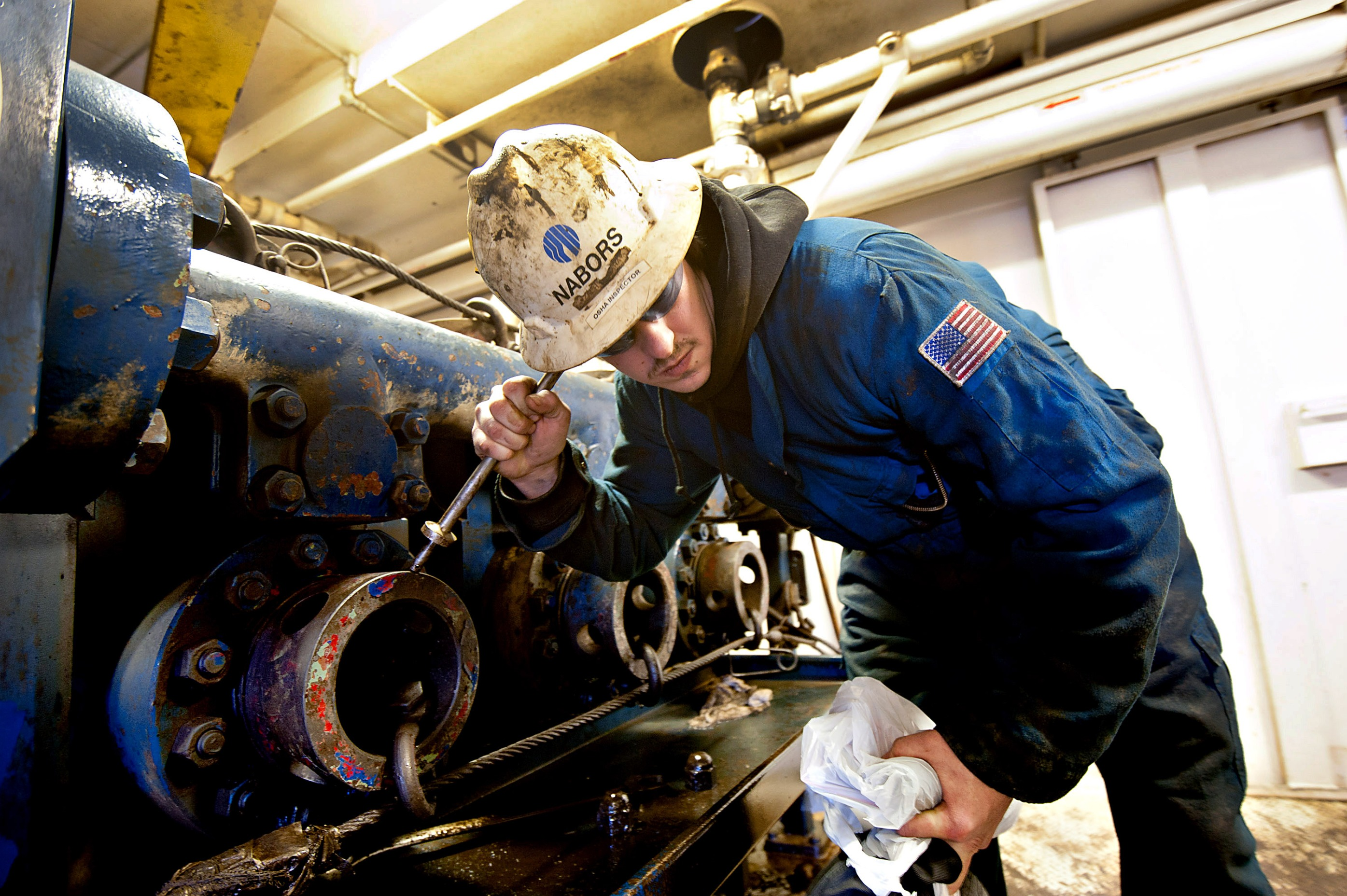 Nabors Industries Ltd. driller Zach Omeara uses a metal rod to listen to the internal operation of a drilling fluid circulation pump during a walk-through of a Nabors crude oil drill rig contracted by Fidelity Exploration & Production Company, a subsidiary of MDU Resources Group Inc., outside New Town, North Dakota, U.S., on Saturday, Feb. 11, 2012.  Photographer: Daniel Acker/Bloomberg