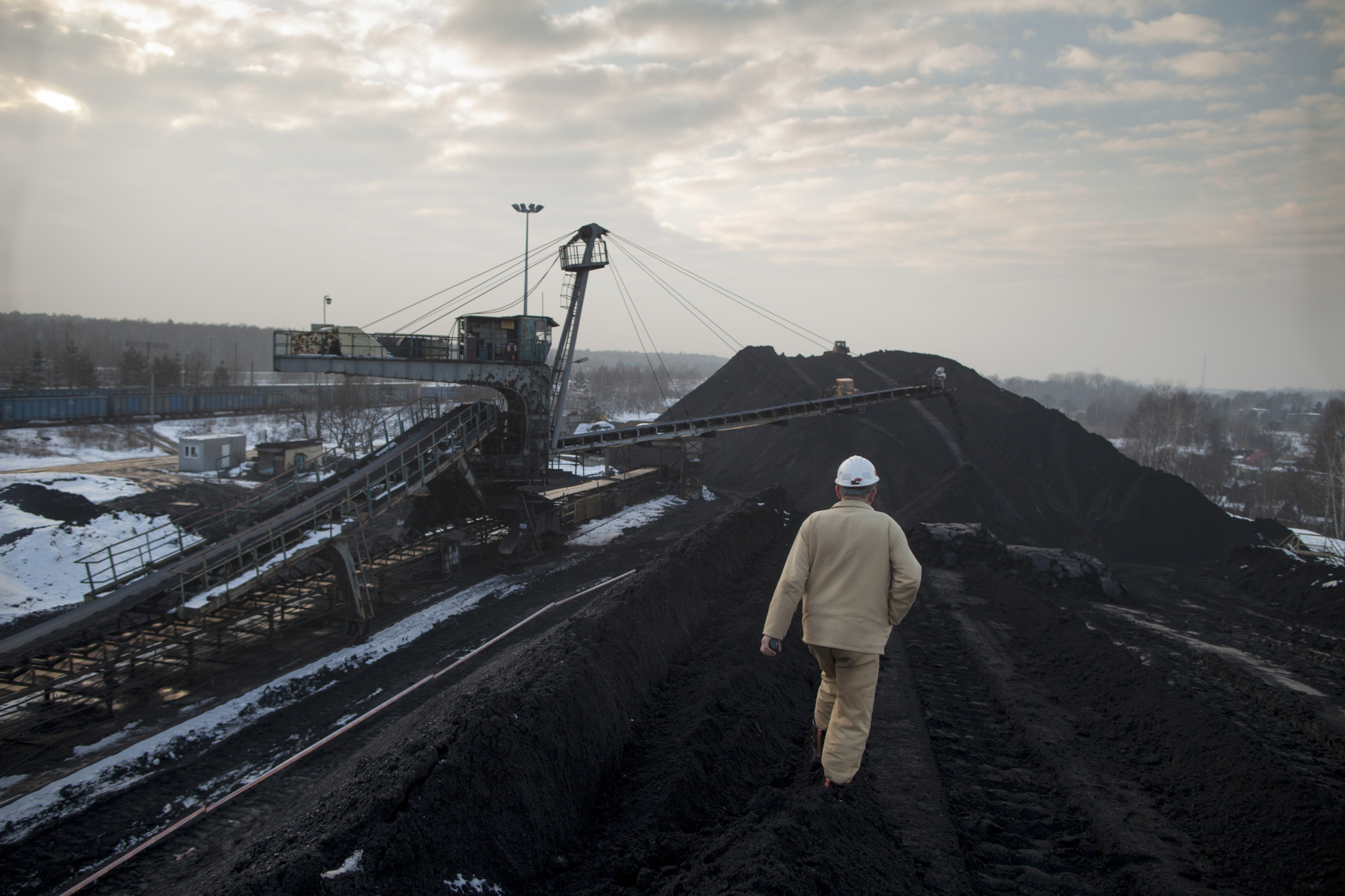 A worker walks across a storage dump of coking coal as a conveyor belt deposits newly processed coal at the Bielszowice mine, operated by Kompania Weglowa SA, in Ruda Slaska, Poland. Photographer: Bartek Sadowski/Bloomberg