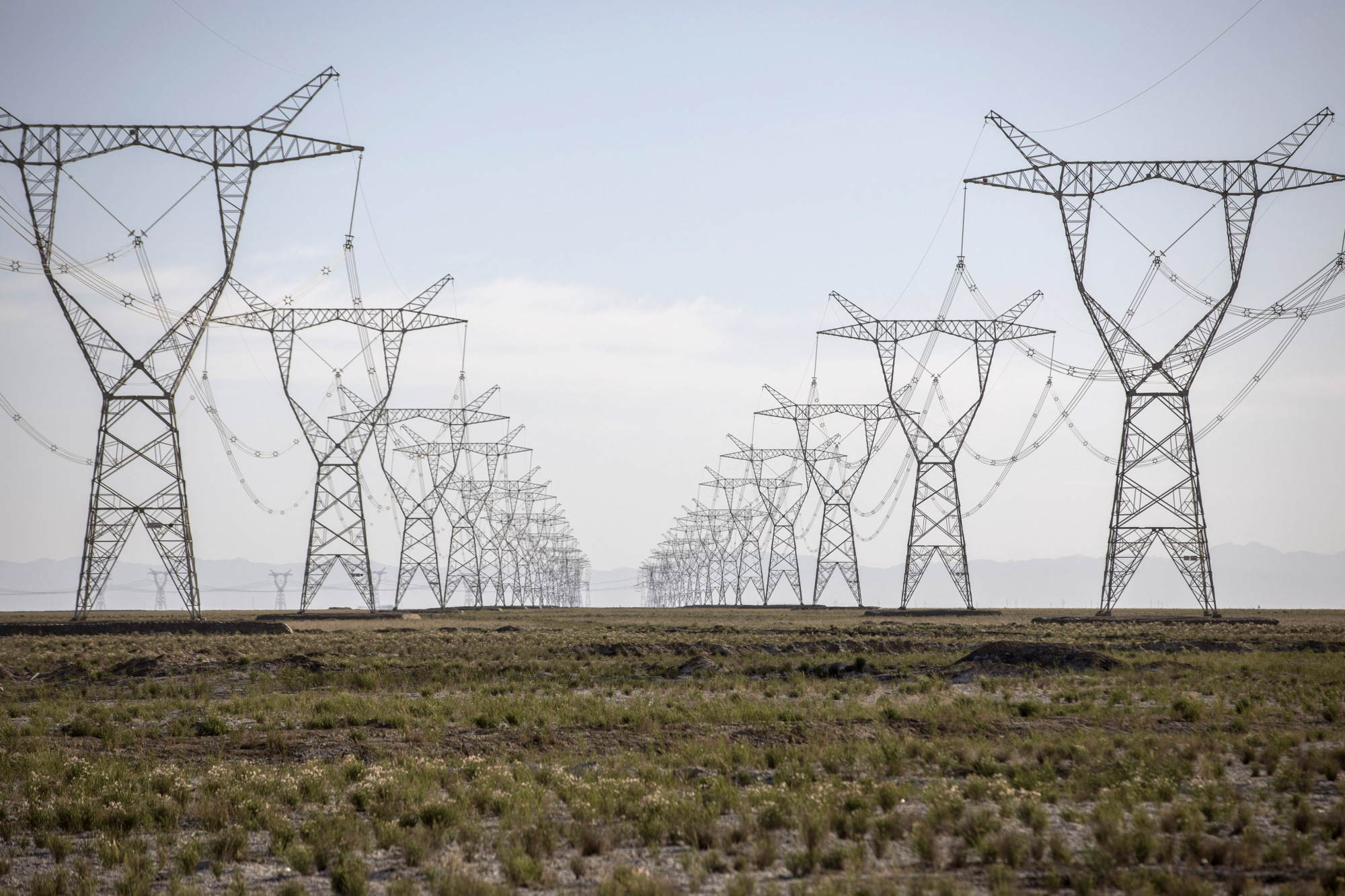 Power lines carrying electricity from the Golmud Solar Park hang from transmission towers on the outskirts of Golmud, Qinghai province, China, on Wednesday, July 25, 2018.
