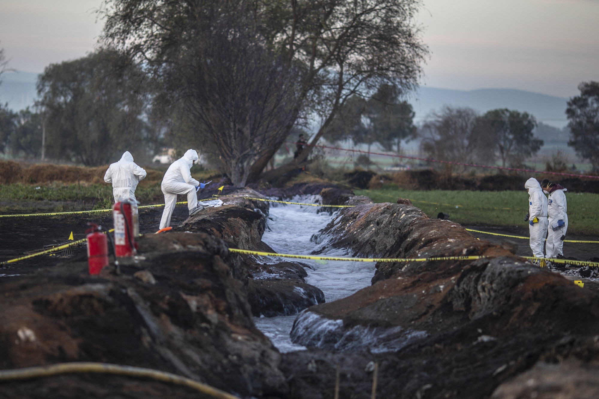 Forensic investigators examine the explosion site. Photographer: Alejandro Cegarra/Bloomberg