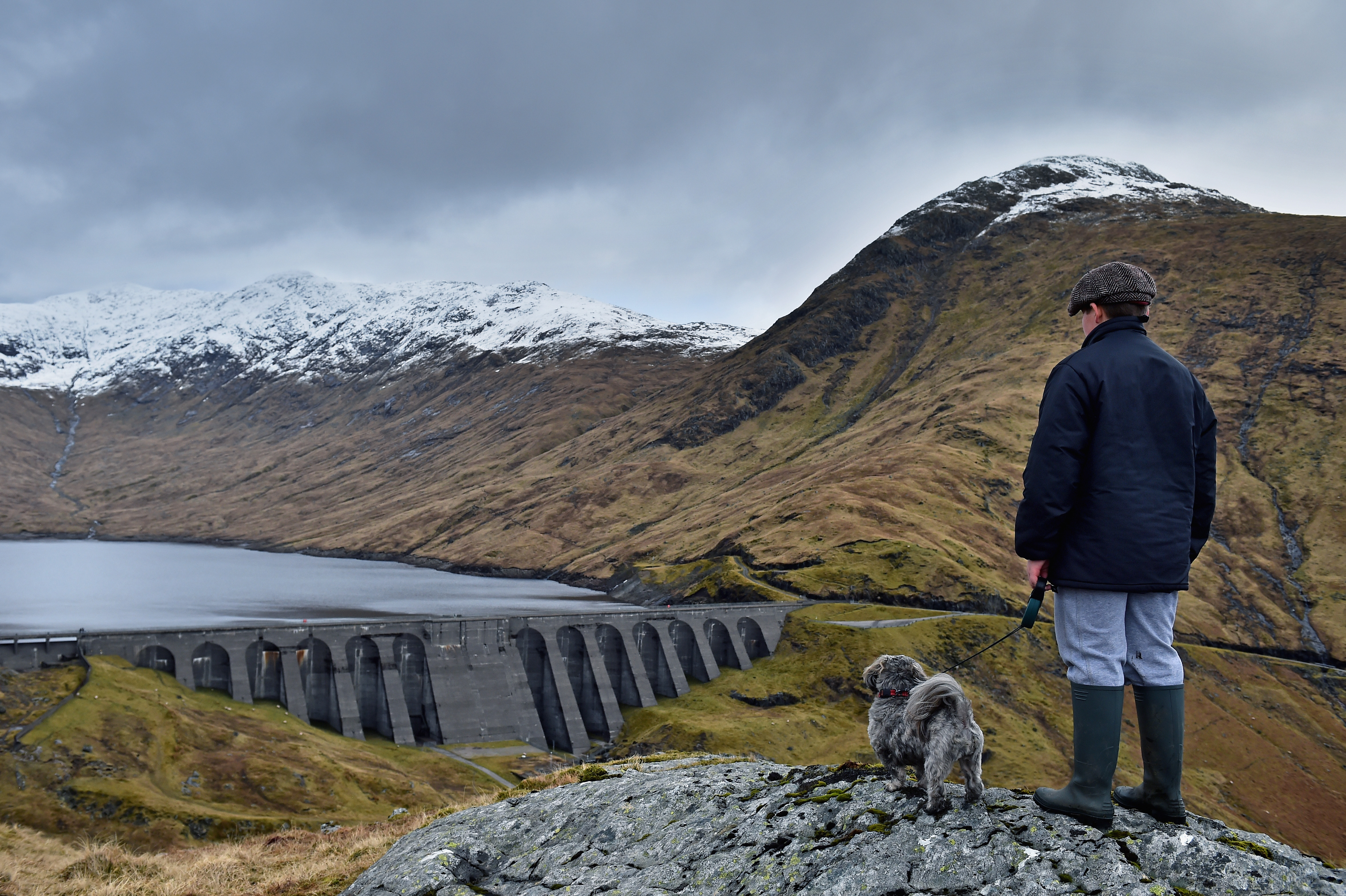 A boy and his dog view Cruachan hydro electric power station in Argyll.