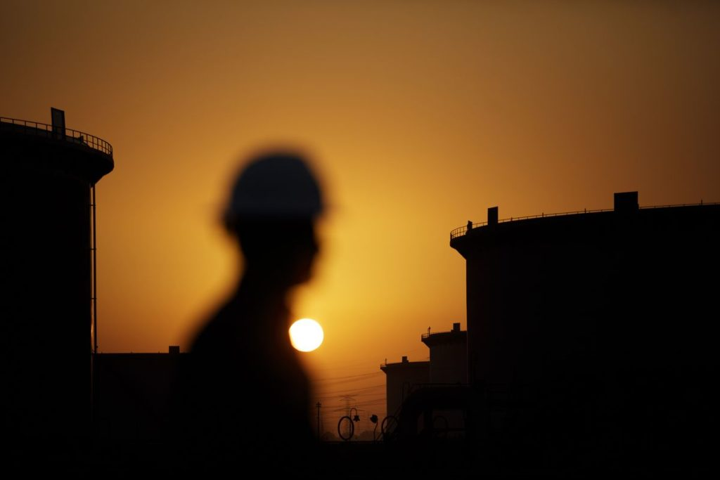 The sun sets over crude oil storage tanks at the Juaymah tank farm, operated by Saudi Aramco, in Ras Tanura, Saudi Arabia, on Monday, Oct. 1, 2018.