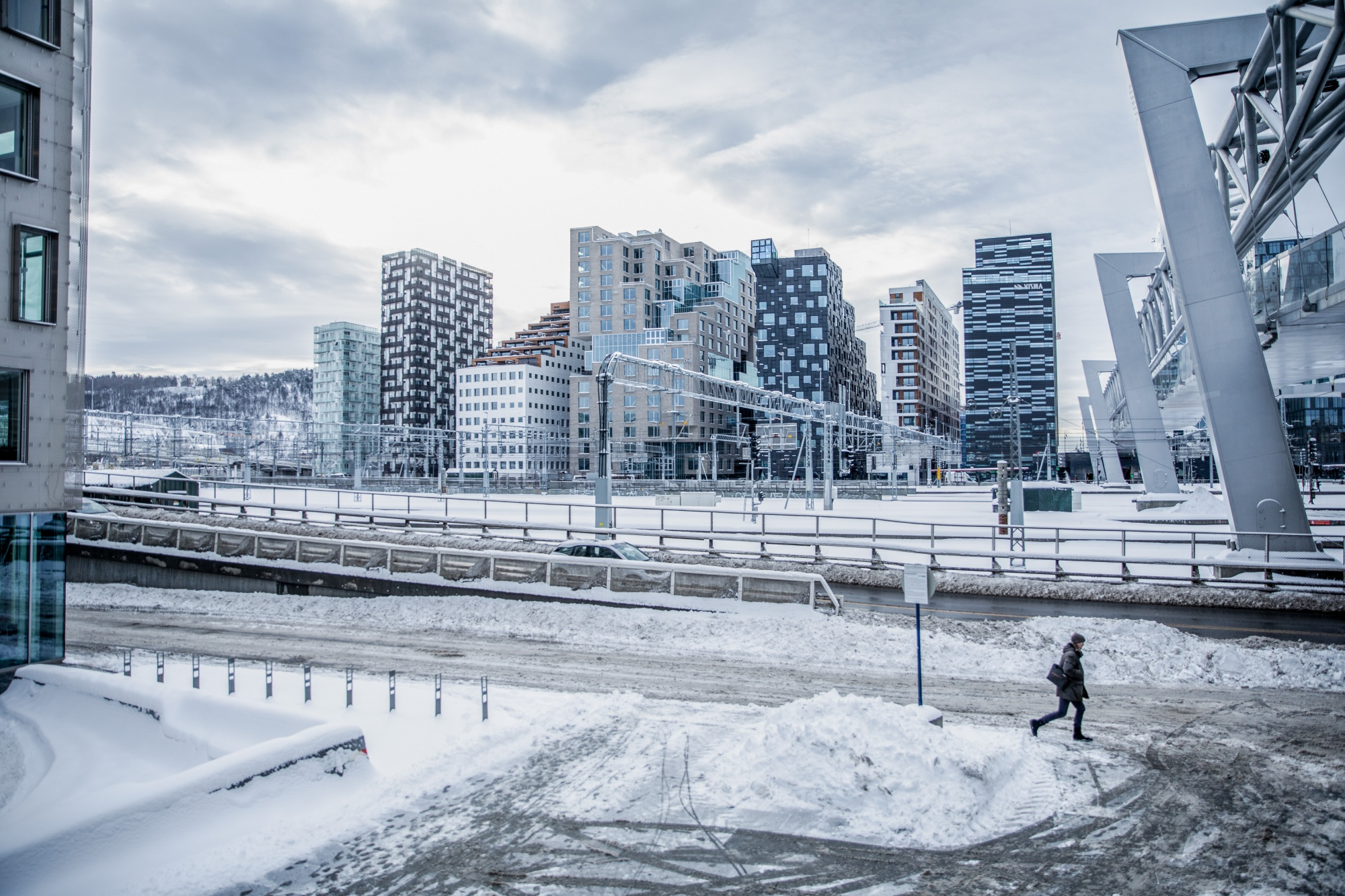 A pedestrian walks past buildings in the Barcode neighborhood of Oslo. Photographer: Odin Jaeger/Bloomberg