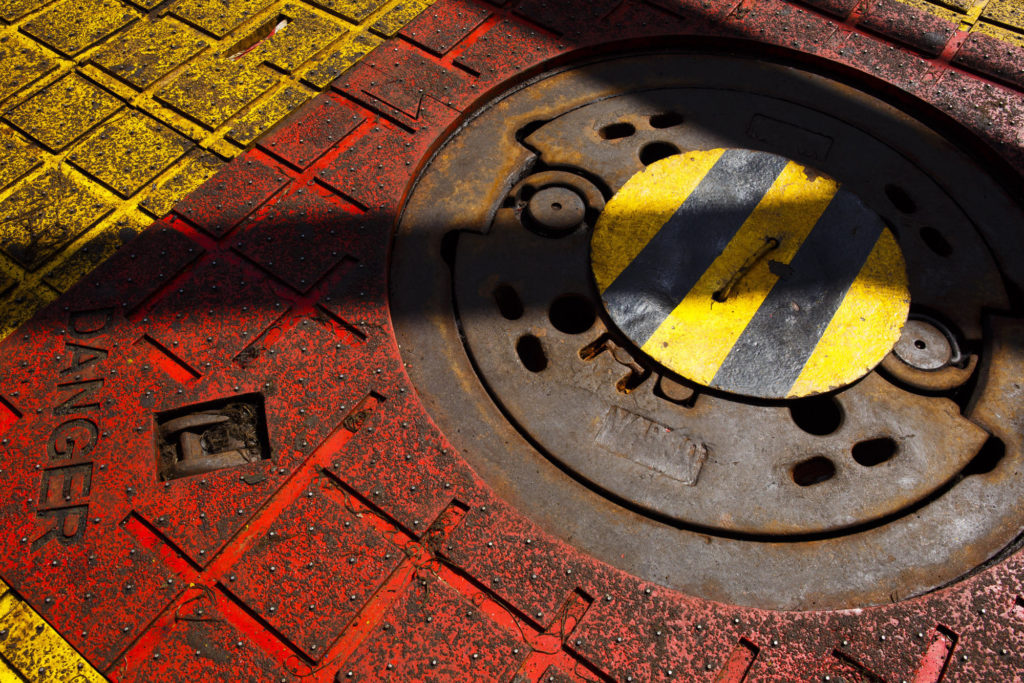 A danger sign sits on the floor beside the covered oil drilling access hole on the Casablanca oil platform, operated by Repsol SA, in the Mediterranean Sea off the coast of Tarragona, Spain. Photographer: Angel Navarrete/Bloomberg