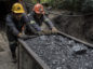 Miners push a wagon of coal outside a mine in Cucunuba, Cundinamarca Department, Colombia, on Friday, July 28, 2017.