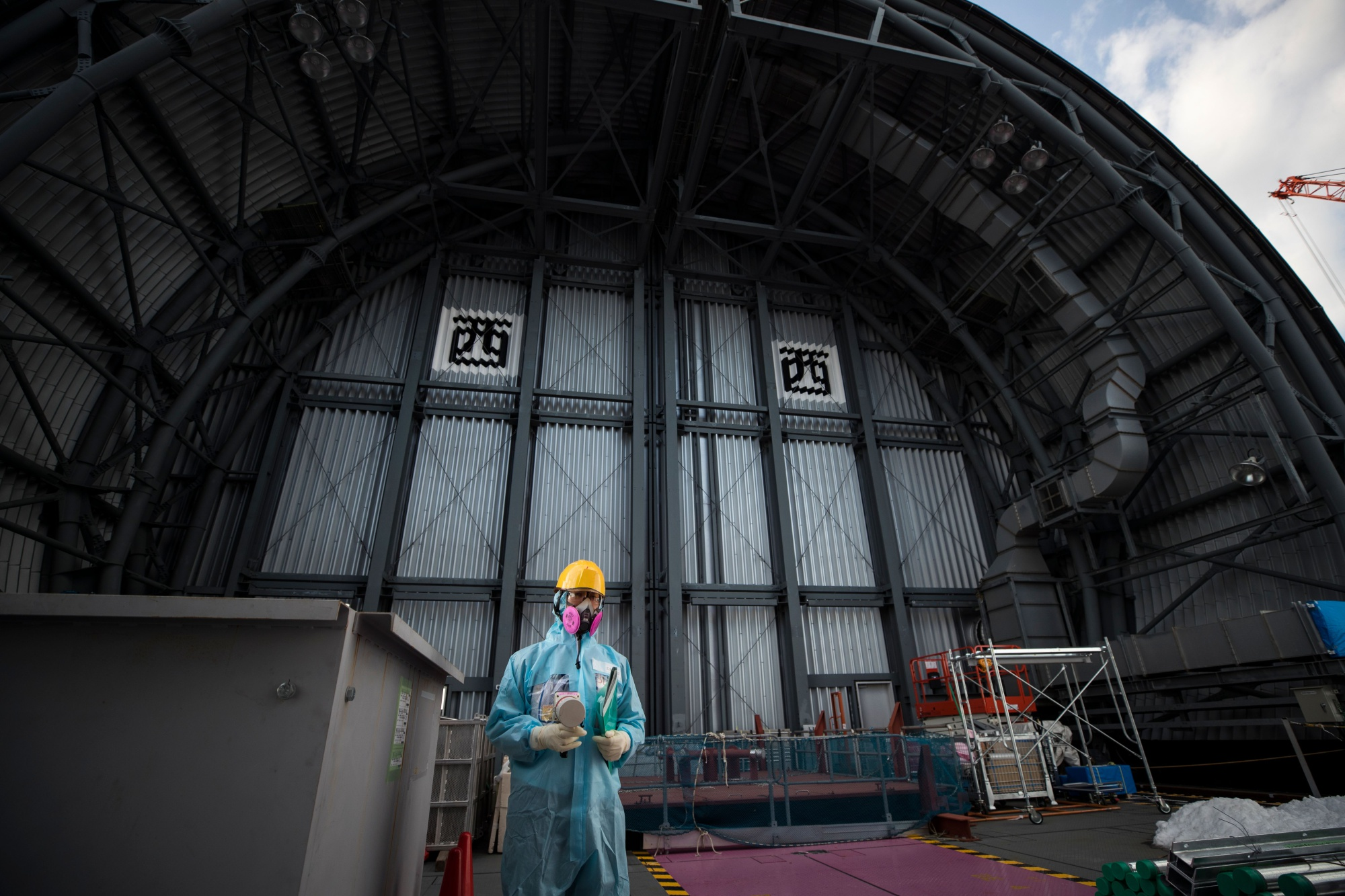 An employee of Tokyo Electric Power Company (TEPCO) holds a geiger counter to measure radiation on the top floor of the company's reactor number 3 at Fukushima Dai-ichi nuclear power plant in Okuma, Fukushima prefecture. Photographer: Behrouz Mehri/AFP/Getty Images