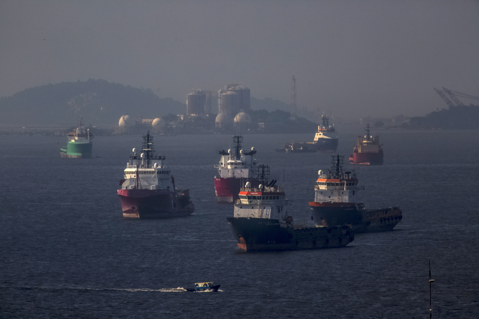 Idle supply vessels float in Guanabara Bay in front of a gas storage facility across from Petrobras's Comperj oil refinery in Rio de Janeiro, Brazil. Photographer: Dado Galdieri
