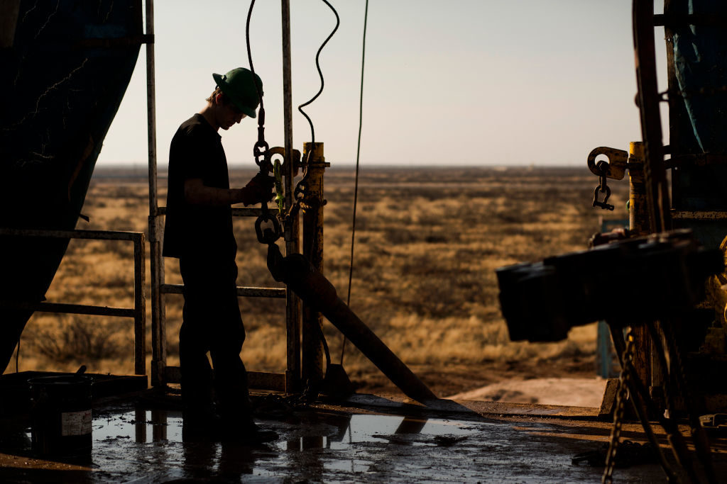 A worker waits to connect a drill bit on Endeavor Energy Resources LP's Big Dog Drilling Rig 22 in the Permian basin outside of Midland, Texas