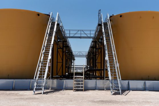 """Separator tanks stand at the Royal Dutch Shell Plc processing facility in Loving, Texas, U.S., on Friday, Aug. 24, 2018. Royal Dutch Shell Plc came through a quarter of volatile oil prices to beat earnings estimates, delivering a surge in cash flow the company said will underpin """"world-class"""" returns to investors. Photographer: Callaghan O'Hare/Bloomberg"""