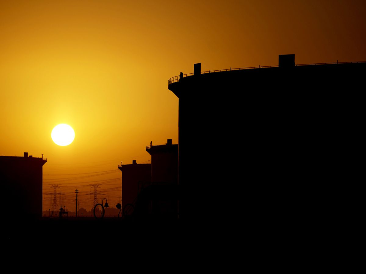 The sun sets beyond crude oil storage tanks at the Juaymah tank farm at Saudi Aramco's Ras Tanura oil refinery and oil terminal in Ras Tanura, Saudi Arabia. Photographer: Simon Dawson