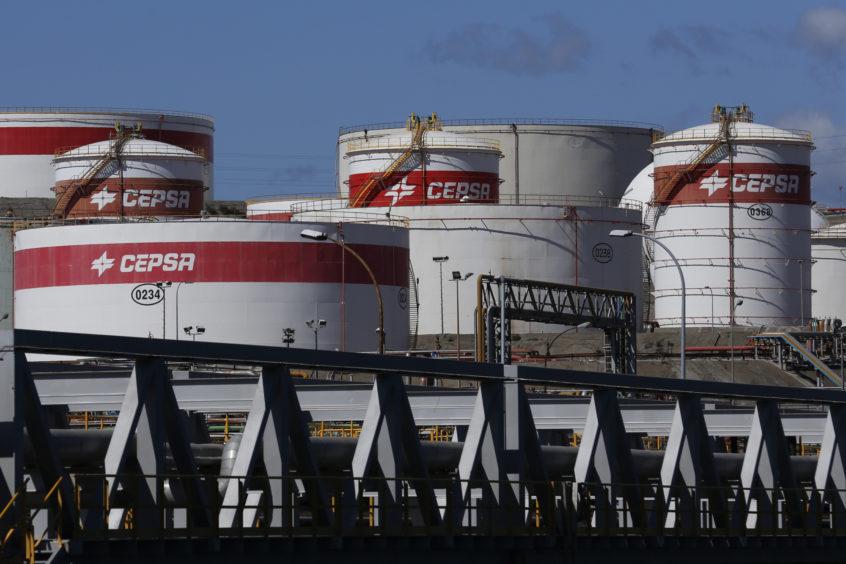 Oil storage tanks sit at the water's edge at the Cia. Espanola de Petroleos (CEPSA) refinery in Algeciras, Spain, on Sunday, March 6, 2016.  Photographer: Luke MacGregor/Bloomberg