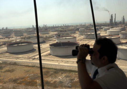 An employee uses binoculars to look out towards the Arabian Sea in the Port Control Center at Saudi Aramco's Ras Tanura oil refinery and terminal in Ras Tanura, Saudi Arabia, on Monday, Oct. 1, 2018.  Photographer: Simon Dawson/Bloomberg